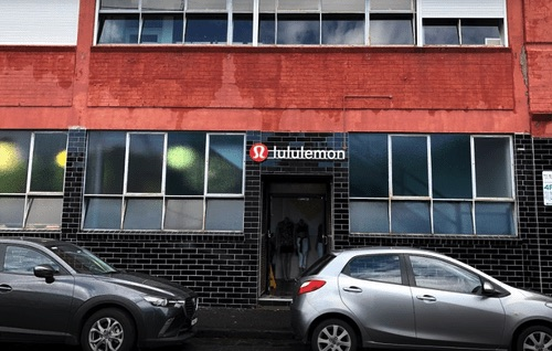 lululemon 工廠直營門市的店面外停著兩台車